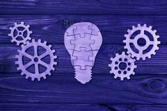 Electric lightbulb from puzzles with gears on a wooden background. vector illustration