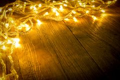 Electric lighted on wooden background Christmas rustic background - vintage planked wood with lights and free text space. Royalty Free Stock Images