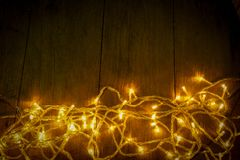 Electric lighted  on wooden background Christmas rustic background - vintage planked wood with lights and free text space. Stock Photo