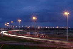 Electric lighting on night the highway. Lighting masts on night Stock Photos