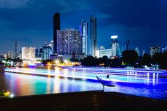 Electric lights flash by on Bangkok's river. stock image