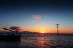 Electric line above water during a fantastic sunset. Stock Images