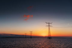Electric line above water during a fantastic sunset Royalty Free Stock Photo