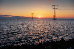 Electric line above water during a fantastic sunset Royalty Free Stock Photography