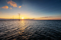 Electric line above water during a fantastic sunset Stock Images