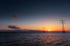 Electric line above water during a fantastic sunset Royalty Free Stock Images