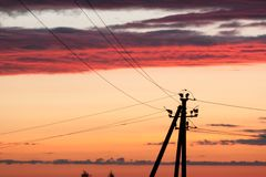 Electric line against colorful sky at sunset. Electric power line against colorful sky at sunset Royalty Free Stock Image