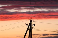 Electric line against colorful sky at sunset. Electric power line against colorful sky at sunset Royalty Free Stock Images