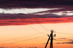 Electric line against colorful sky at sunset. Electric power line against colorful sky at sunset Stock Photos