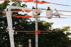 Electric linemen power-line. Electricians linemen working outside on power lines Stock Photos