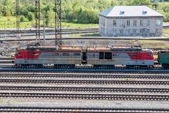 Electric locomotive with freight carriages passes through the railway station. In the village Royalty Free Stock Images