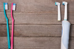 Electric and manual toothbrushes on the wooden background Royalty Free Stock Photo