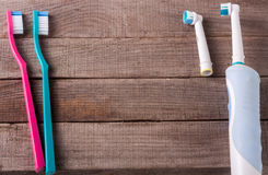 Electric and manual toothbrushes on the wooden background Stock Image