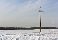 Electric mast and agriculture field in snow. Royalty Free Stock Photo