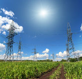 Electric masts and road in green field Stock Image