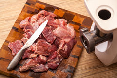 The electric meat grinder and the cut meat Royalty Free Stock Images