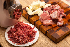 The electric meat grinder, forcemeat, onions and the cut meat Stock Photo
