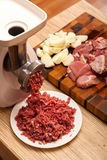 The electric meat grinder, forcemeat, onions and the cut meat Royalty Free Stock Photos