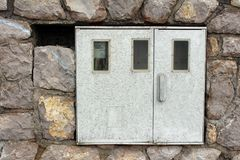 Electric meter box mounted on stone wall. With one out of three meters inside and working Royalty Free Stock Image