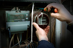 Electric meter. The electrician changes the old electric meter for the new Royalty Free Stock Images