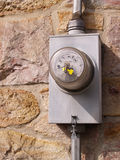 Electric meter by a stone wall stock photo