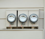 Electric Meters. Three Electric Meters, mounted on a wall stock photo