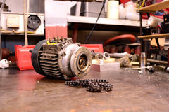 Electric motor and chain. Various rejected broken spare parts from electronics workbench Stock Photo
