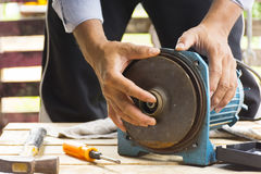Electric motor  and man working equipment repair on wooden floor background.Background mechanic or equipment Stock Photo