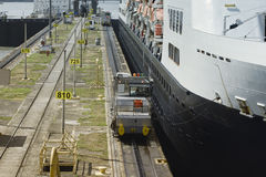 Electric mules steering large cruise ship at the first locks Royalty Free Stock Images