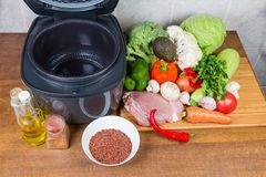Electric multi-cooker with empty pot among of raw foods. Modern electric automatic household multi-cooker with open lid and empty inner pot among of various raw stock image