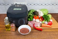 Electric multi-cooker among of raw foods on cook table. Modern electric automatic smart household multi-cooker among of various raw foods on a cook table royalty free stock photography