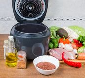 Electric multi-cooker among of raw foods on table closeup. Modern electric automatic household multi-cooker with open lid among of various raw foods on a cook stock photography
