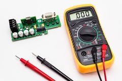 Electric multimeter with red and black probe, display indicating zero, with printed circuit board. Isolated on a white background stock photos