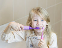 Electric and ordinary toothbrushes in the hands of beautiful girls. royalty free stock photo