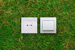 Electric outlet and light switch on a grass Royalty Free Stock Photos