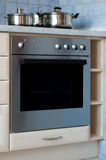 Electric oven. Built-in stainless steel electric oven with cooking pots on stove Stock Photo