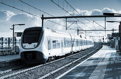 Electric passenger train goes near railway platform. In Amsterdam, Netherlands. Blue toned monochrome photo Stock Photo