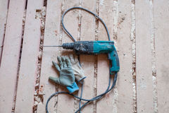 Electric perforator drill and working gloves are on the dirty and dusty wooden floor Stock Photos