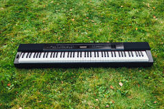 Electric piano on grass background Royalty Free Stock Photography