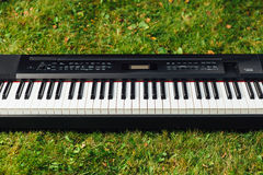 Electric piano on green grass background Stock Images