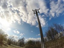 Electric pillar and wires in the field in the spring Stock Images