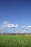 Electric pillars. Power station and electric pillars on green field Stock Image