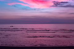 Electric Pink Tropical Sunset over the sea. Portrait aspect image of fishermen at sea on a boat, beneath a vivid pink and sky blue sunset sky. Taken on Lombok royalty free stock images