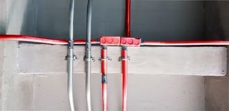 Electric pipes and Red electric pipes for safety systems in building,Cable wiring,Metal pipes in Construction and fire sprinkler. On Red pipe are hanging from royalty free stock image