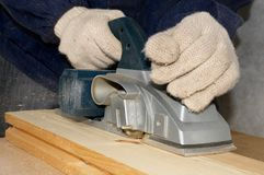 Electric planer. The worker planes the wood Stock Photography