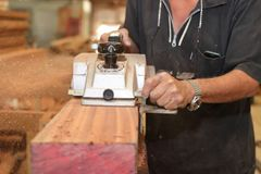 Electric planer is being worked with hands of senior carpenter in carpentry workshop. Selective focus and shallow depth of field. Royalty Free Stock Photo