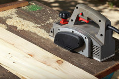 The electric planer. Is lying on a wooden table Royalty Free Stock Images