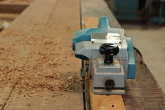 Electric planer with sawdust on the wood piece in carpentry workshop Stock Photography