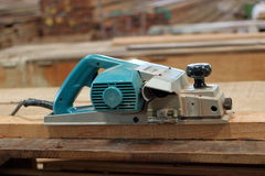 Electric planer on the wooden plank in carpentry workshop.  Stock Image