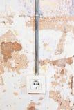 Electric plug. Electric wall plug at a mixed textured wall shades stock photos